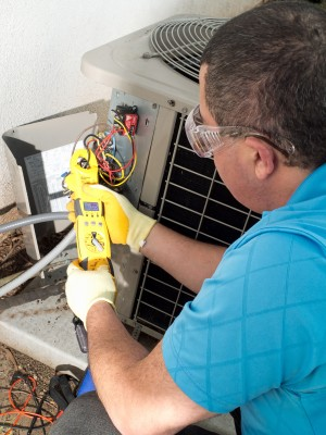 Boulder air conditioner repair man checks resistance with an ohmmeter
